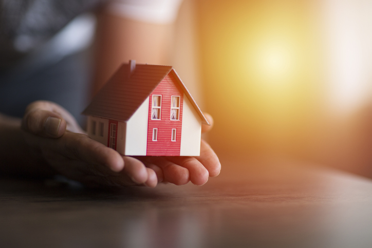 Business man hand hold the house model saving small house